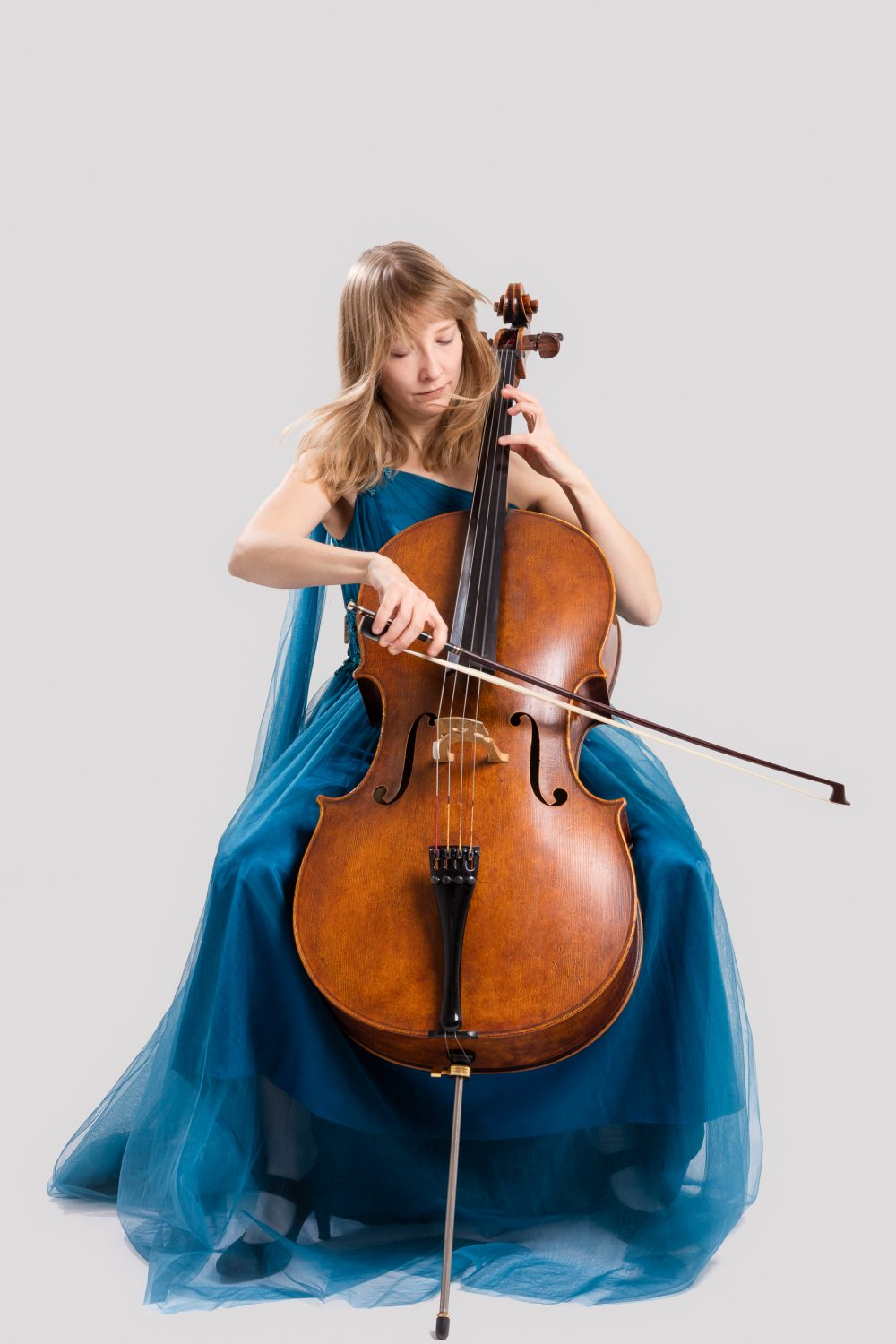 Isabel Gehweiler playing her cello in blue dress