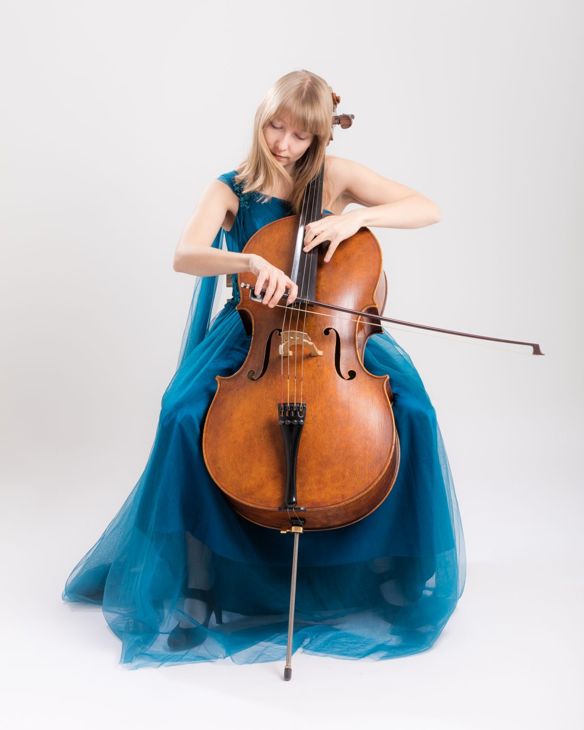 Isabel Gehweiler in blue dress playing cello