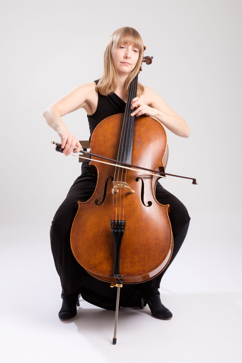 Isabel Gehweiler playing cello in black dress