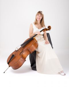 Isabel Gehweiler with cello, in white dress sitting on chair